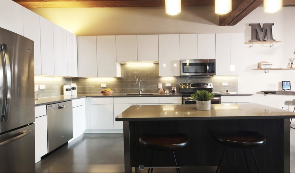 This photograph shows a finished kitchen at an multi-family apartment building in New Jersey. The cabinets are a modern white, the appliances are stainless steel and there is a custom island in the kitchen