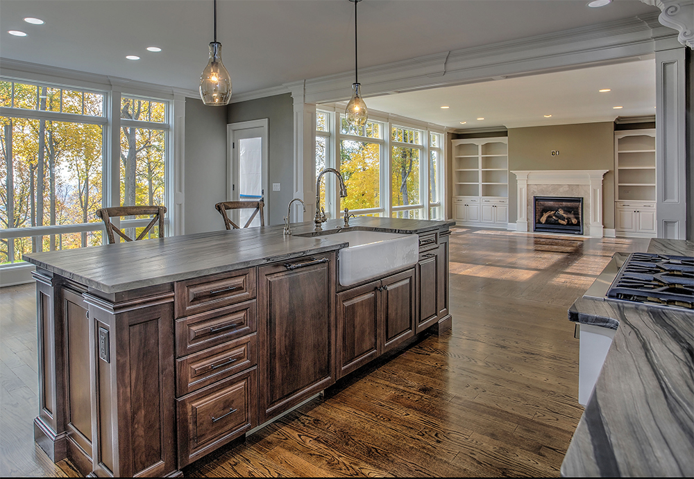 Kitchen island with farm sink are pictured here as well as a custom bookcase we built in the living room