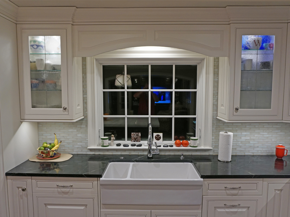 Photo of renovated kitchen's new sink, glass cabinets and arched moulding
