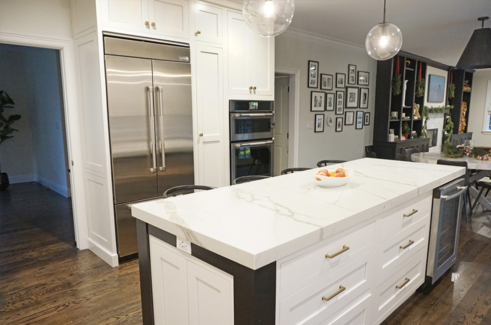 The two-tone center island and white wall cabinets are shown in this photo